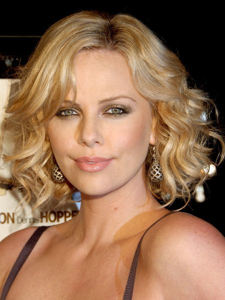 Charlize Theron demonstrates safe use of curling iron